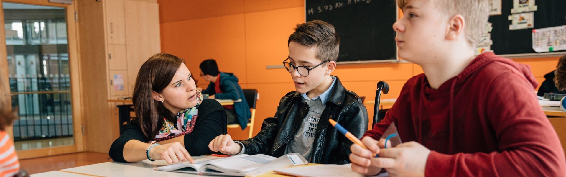 Zwei Schüler beim Lernen in der Schule mit einer Lehrerin
