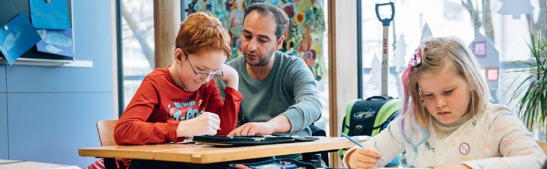 Lehrer erklärt einem Schüler etwas im Hefteintrag
