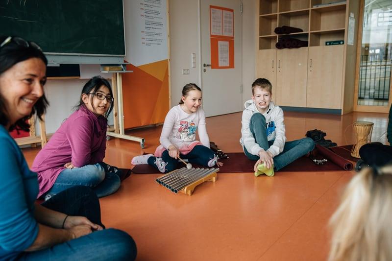 Mehrere Kinder mit Betreuerin während der Musiktherapie in der Ernst Barlach Schule der Stiftung Pfennigparade