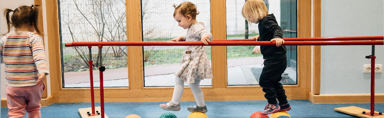 Kinder bei Übungen am langen Barren mit Igelbällen zur Förderung des Gleichgewichts