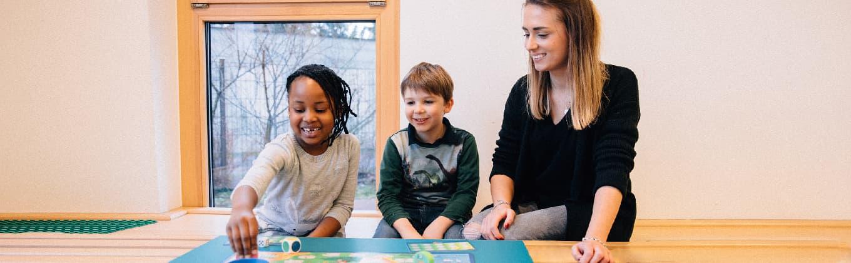 Zwei Kinder und eine Betreuerin spielen