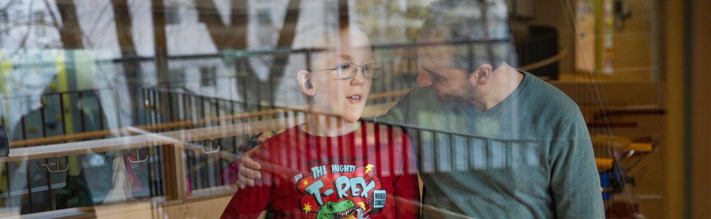 Junge mit seinem Betreuer hinter einer Fensterscheibe