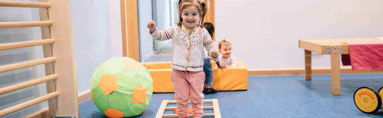 Mädchen übt Laufen und zwei Kinder spielen