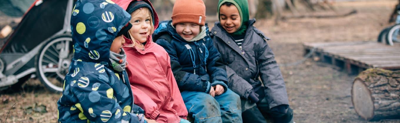 Vier Kinder sitzen lachend im Außenbereich des Waldkindergarten