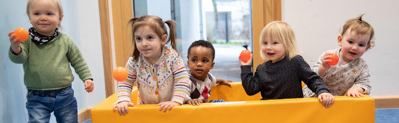 Fünf Kinder spielen im Kinderhaus mit Bällen