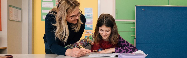 Betreuerin unterstützt Schülerin beim Lernen
