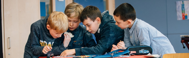 Vier Jungen besprechen Lerninhalte in der Schule