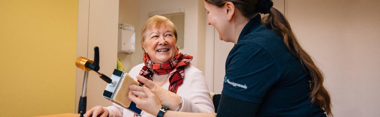 Ergotherapeutin der Stiftung Pfennigparade bei Verwendung eines Hilfsmittels mit einer Patientin