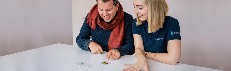 Logopädin der Stiftung Pfennigparade spielt mit einem Patienten Memory