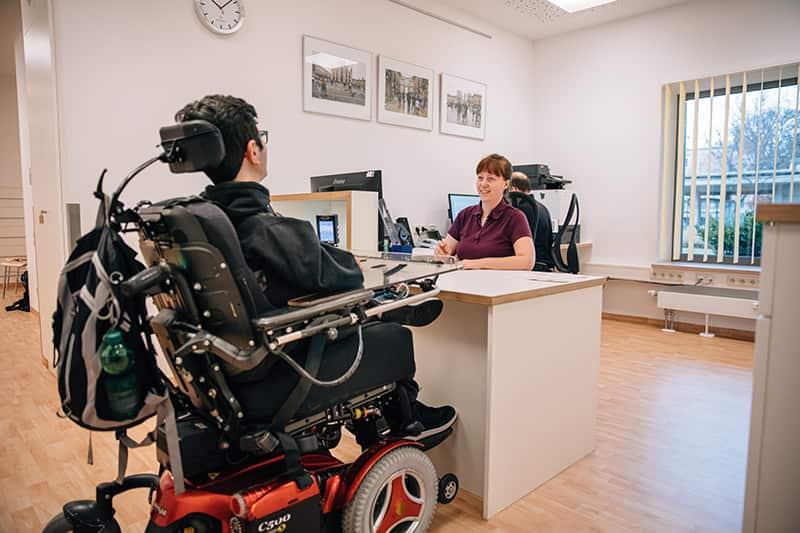 Arzthelferin und Patient bei der Anmeldung am Empfang im MZEB der Stiftung Pfennigparade