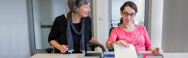 Frau mit Beraterin bei der Ablage von Papieren