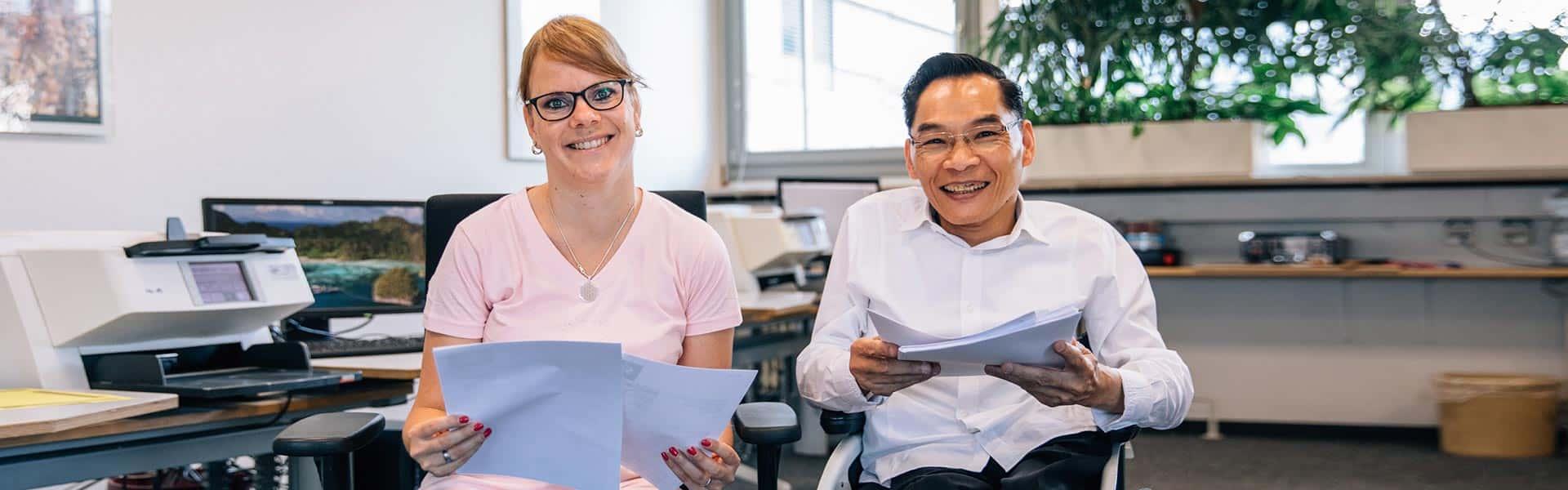 Eine Frau und ein Mann sitzen vor einem Arbeitsplatz und haben Unterlagen in ihren Händen