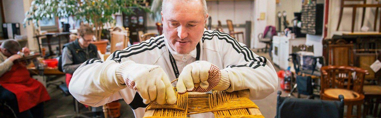 Mann im Rollstuhl beim Flechten in der Werkstatt