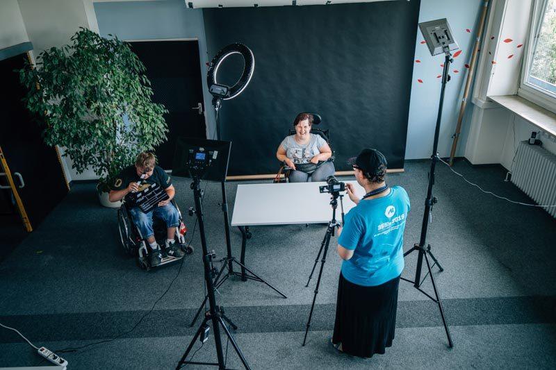 Drei Werkstattmitarbeiter*innen beim Videodreh im Studio vom Medienservice