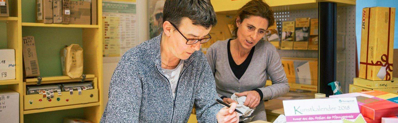 Zwei Frauen im Gespräch in der Verkaufsstelle der Postshops der Pfennigparade