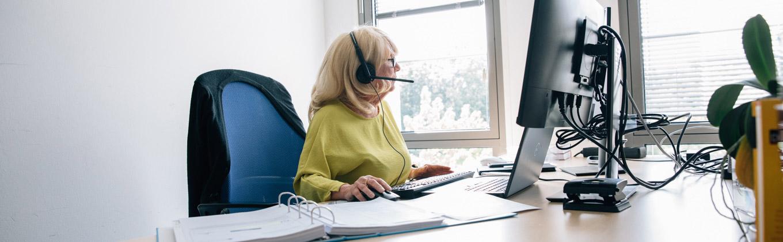 Frau mit Headset an einem PC