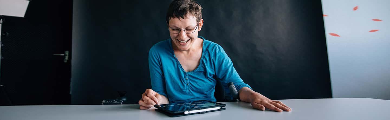 Eine Frau arbeitet mit einem iPad und strahlt
