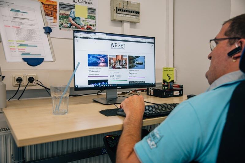 Ein Werkstatattmitarbeiter bei der Webseitenpflege in der Medienschmiede
