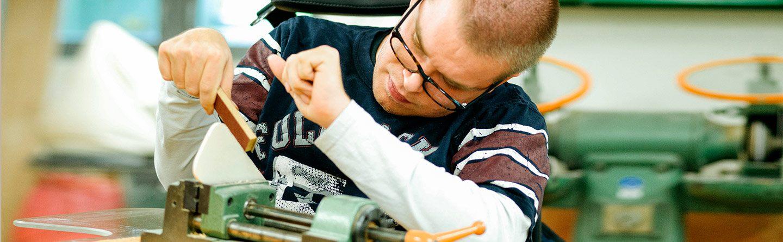 Ein Werkstattmitarbeiter im E-Stuhl schleift einen Gegenstand mit Schleifpaier ab, der in einer Schraubzwinge fixiert ist
