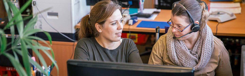 Eine Mitarbeiterin an ihrem Arbeitsplatz Büroservice im Gespräch mit Ihrer Gruppenleiterin