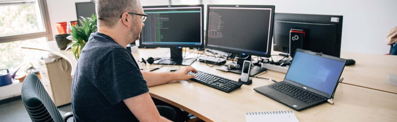 Ein Mitarbeiter sitzt an seinem Computer beim IT-Support