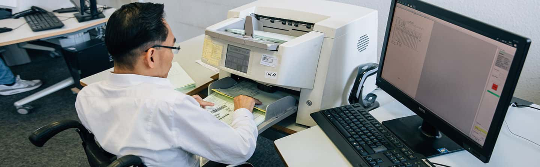 Mitarbeiter beim Einscannen von Dokumenten