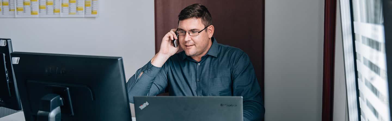 Mann telefoniert und sitzt an einem PC