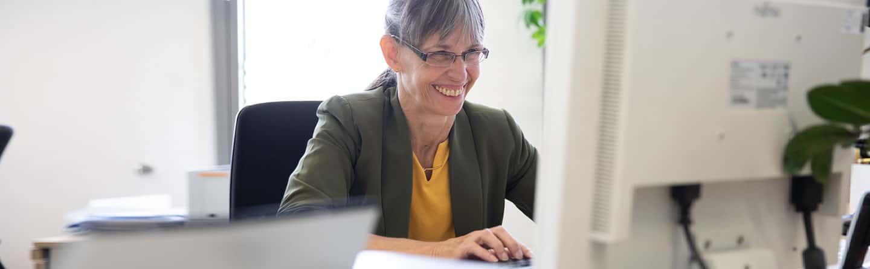 Frau sitzt lachend an einem PC