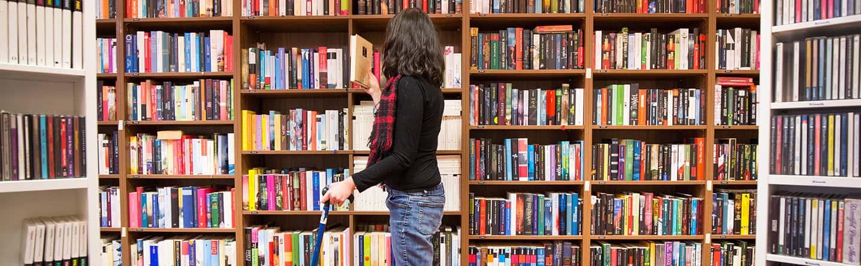 Frau am Regal sucht Bücher aus