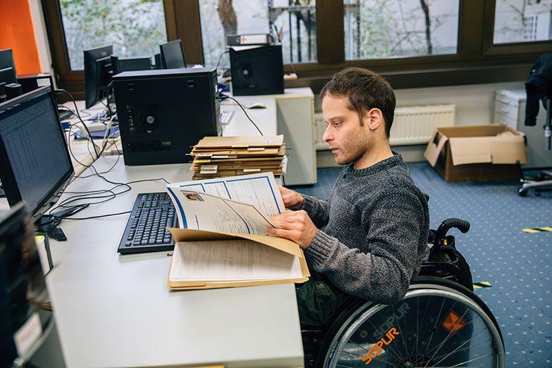 Ein Mann im Rollstuhl blättert in einer Akte an seinem Arbeitsplatz in der Datenerfassung