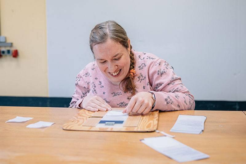Eine Frau sitzt an einem Tisch und verpackt mit Hilfe eines Klemmbretts Broschüren der Stiftung Pfennigparade