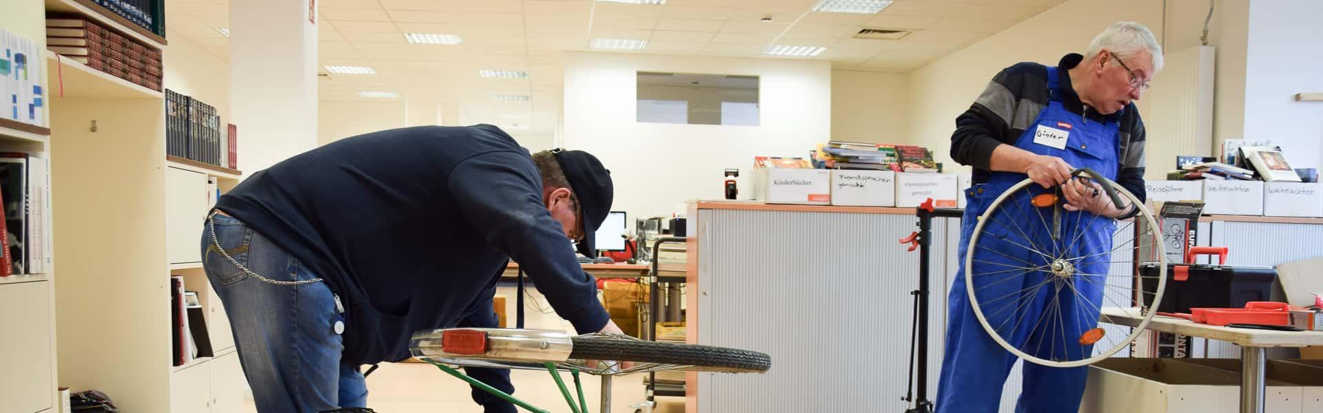 Zwei Mitarbeiter bei einer Fahrrad-Reparatur