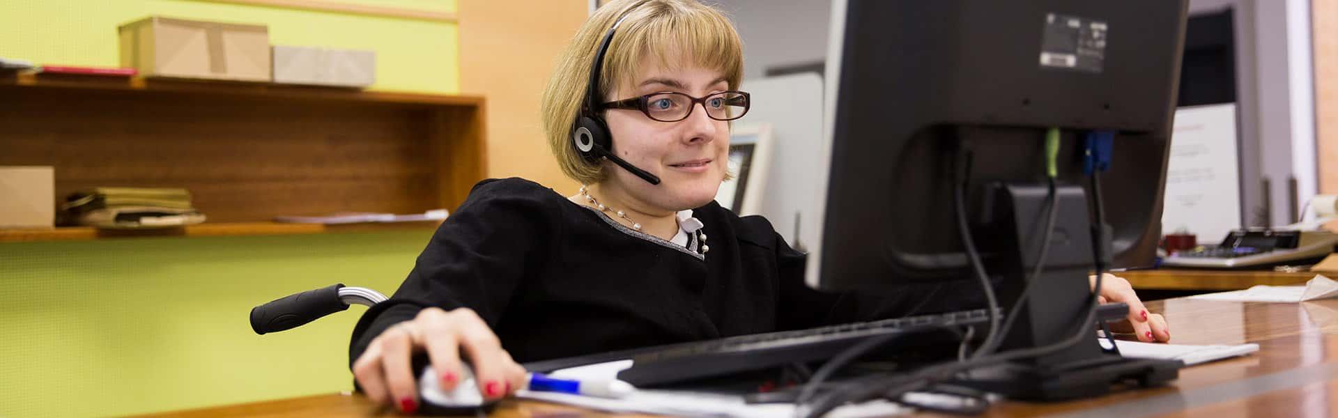 Mitarbeiterin am Computer mit Headset