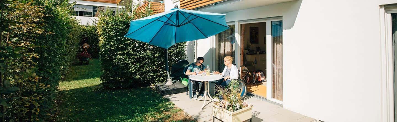 Patientin und Gast auf der sonnigen Terasse ihrer Mietwohnung