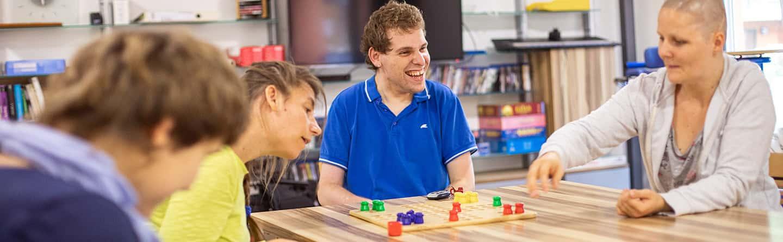 Mehrere Patienten mit Behinderung spielen ein Brettspiel
