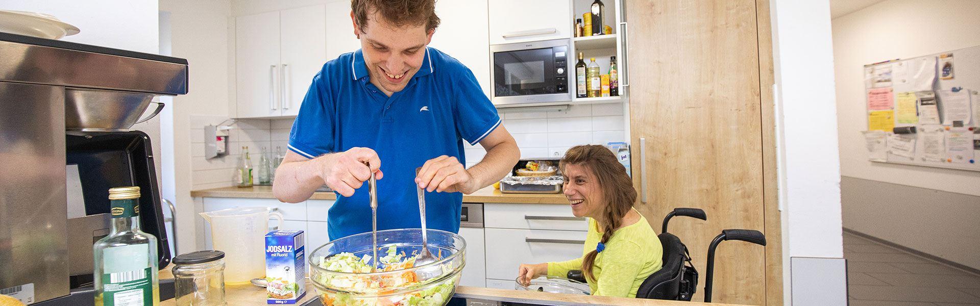 Ein Bewohner und eine Bewohnerin beim Zubereiten eines Salats
