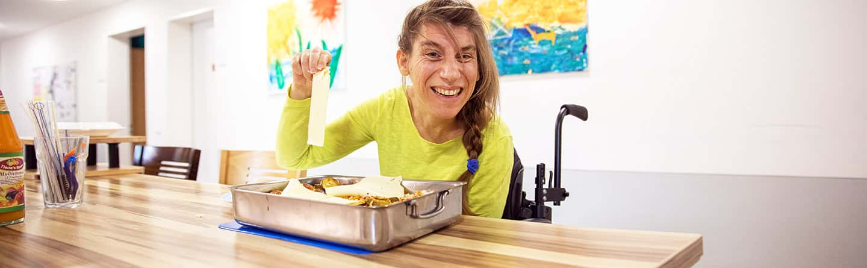 Bewohnerin lachend beim Kochen