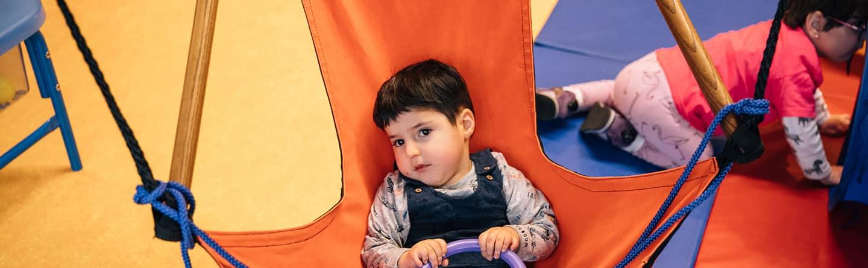 Kind liegt im Hängestuhl und spielt
