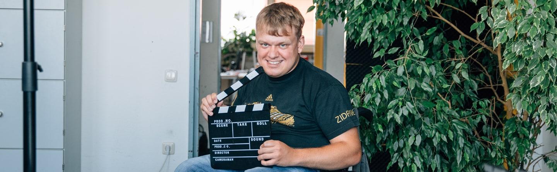 Werkstattmitarbeiter lachend mit Filmklappe