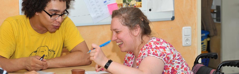 Eine Frau im Rollstuhl spielt Kniffel mit einem Betreuer