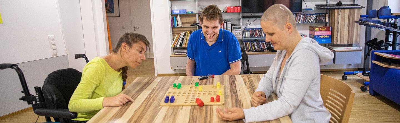 Drei Bewohner spielen gemeinsam ein Brettspiel