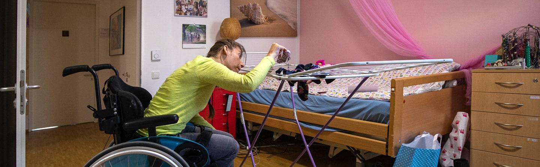 Frau im Rollstuhl beim Wäsche aufhängen