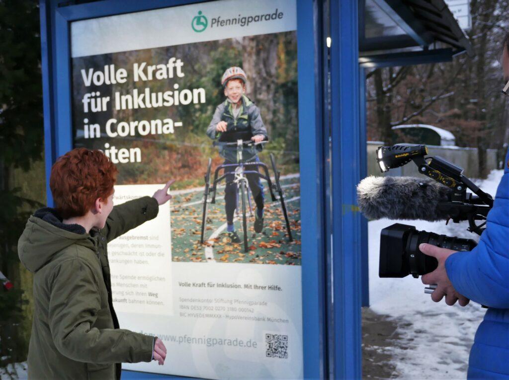 Tim steht vor einem Plakat, das ihn auf einem Racerunner, einem Rennlaufrad, zeigt