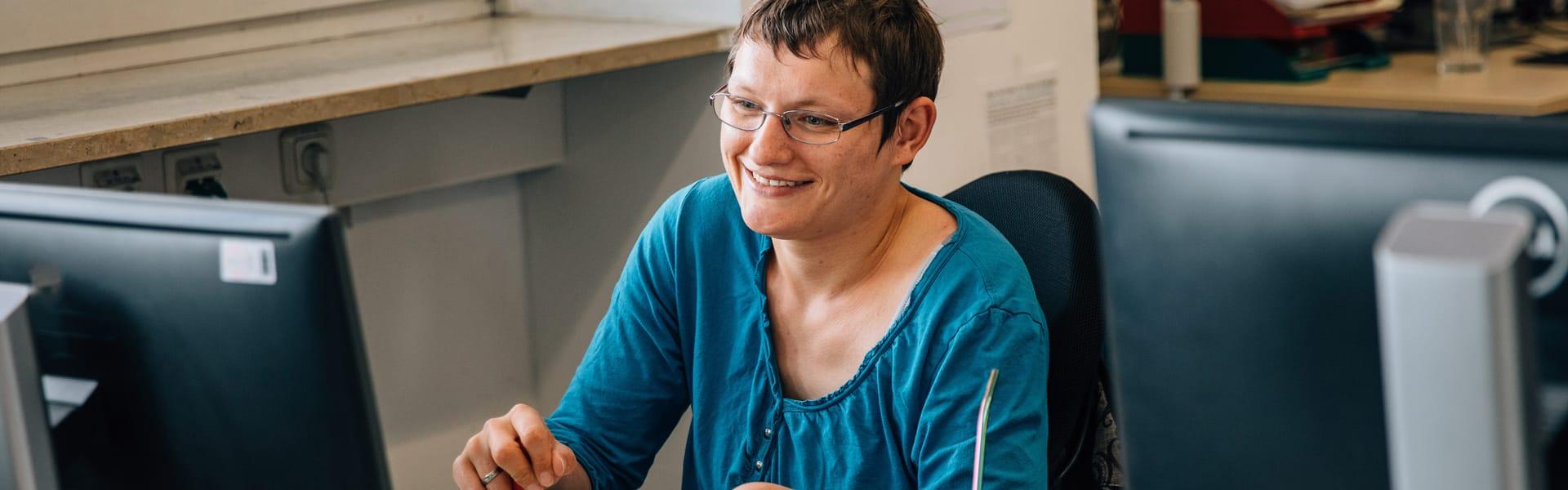 Frau arbeitet mit Freude am Computer
