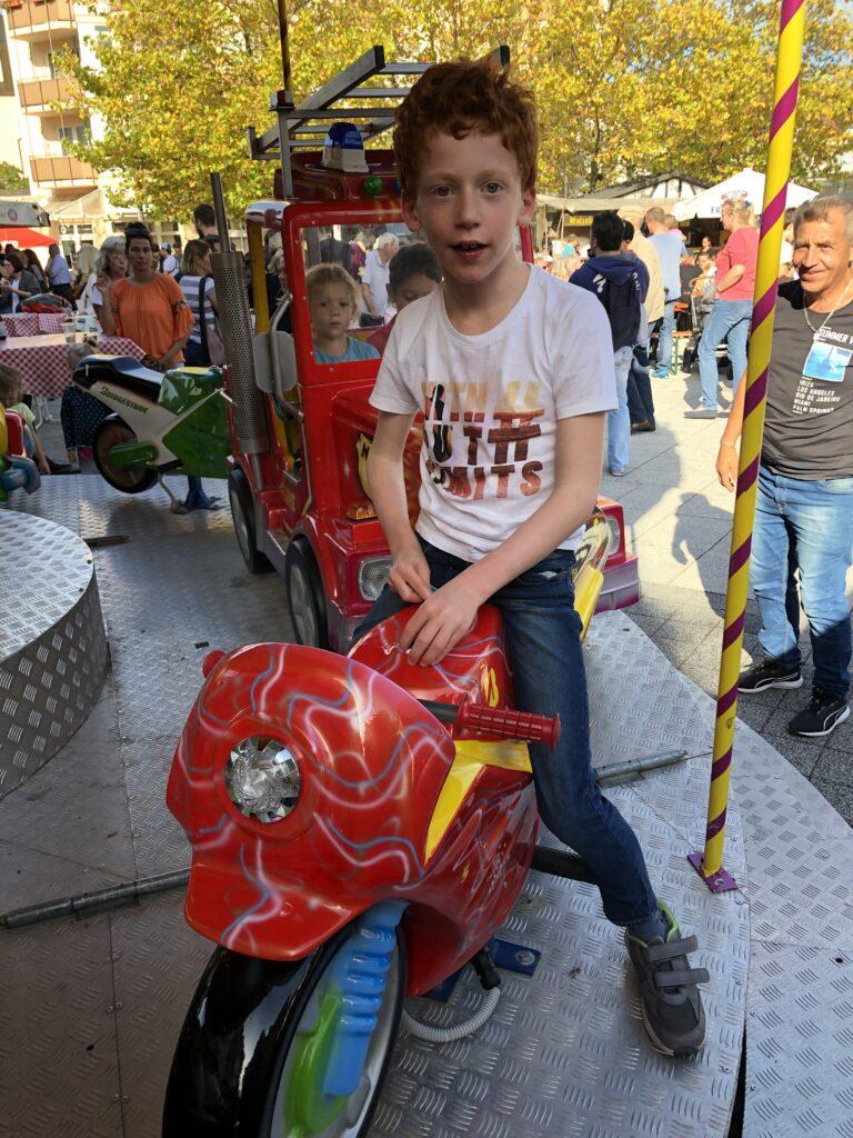 Junge auf Motorrad im Jahrmarkt-Karussel