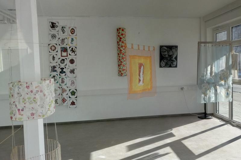 Bunte Seidentücher hängen im Ausstellungsraum