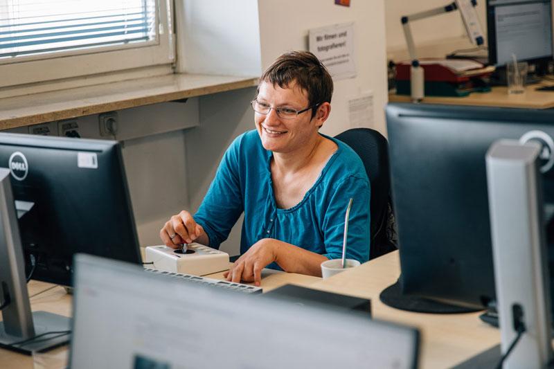 Frau arbeitet mit einer Joystick-Maus am Computer