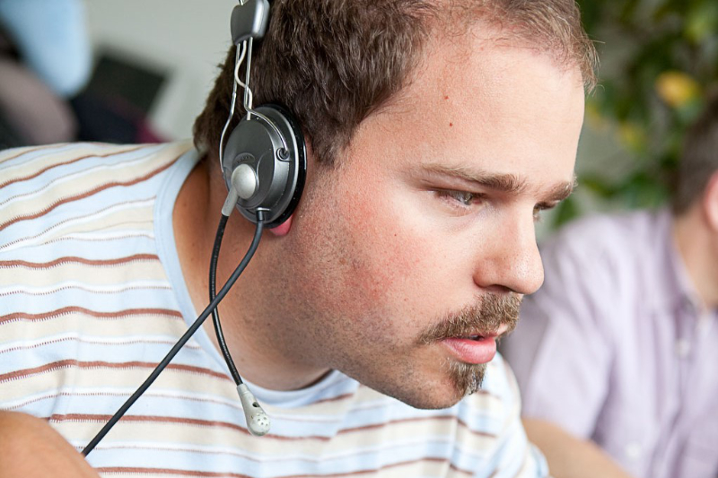 Blinder Mann arbeitet mit Headset auf dem Kopf und Spezialtastatur mit Braillezeile am Computer