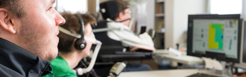 Drei jüngere Männer sitzen im Rollstuhl vor mehreren Computern. Im Vordergrund ist eine Person zu sehen, dahinter unscharf noch zwei weitere. Aufgrund von Körperbehinderungen sie im Elektrorollstuhl und sind beatmet.