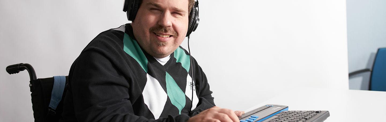 Blinder Mann sitzt mit Headset auf dem Kopf und Spezialtastatur mit Braillezeile am Computer und lächelt in die Kamera